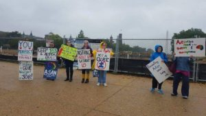 "This is an image of anti-Autism Speaks protesters holding signs at the National Mall. There is a lot of construction in the background. The signs are the same as the ones from the other picture of the group, except for the addition of a person in a blue raincoat and noise cancelling headphones wearing a sign that states, ""Finding a Cure Won't Help Us.""."