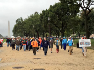 A long line of Autism Speaks supporters walk around the National Mall. It is cloudy and the Washington Monument is visible in the background.