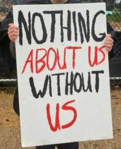 "This is an image of a person holding a sign. Their face and legs are out of the frame. The sign reads, ""Nothing About Us Without Us."""