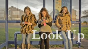 "Three women are sitting at a bus stop. Two are looking at their phones and the third is not. The text, ""look up"" is superimposed over the image."