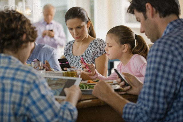 A mother, a father and two children are looking at their cell phones and tablets while sitting together at the dinner table.