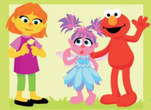 This image shows Elmo introducing Abby Cadabby to the new muppet, Julia. All three are puppets. Elmo is red with an orange nose. Abby Cadabby is pin. She has pink and purple hair, and wears a blue fairy costume. Julia is yellow with orange hair and an orange nose. She is wearing a purple t-shirt and green pants, and is looking at a flower instead of making eye contact with Abby or Elmo.