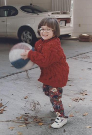 This is an image of Sara Luterman as a child. She is wearing a red sweater and leggings. She has brown hair and glasses. Sara is holding a basketball that is larger than her head.