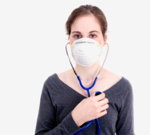 A white woman with dark hair holds a stethoscope to her own chest. She is wearing a paper mask and a gray shirt.