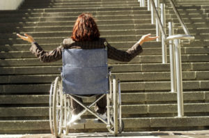 A white person with brown hair is sitting in a wheelchair at the bottom of a flight of stairs. The person is gesturing in frustration.