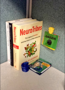 "Three books are in the corner of a cubicle. The titles are ""Neurotribes,"" ""Rosemary,"" and ""Loud Hands."" Beside them, a color communication badge is attached to the cubicle wall. A stim toy and Einstein sticky notes are holding the books in place."