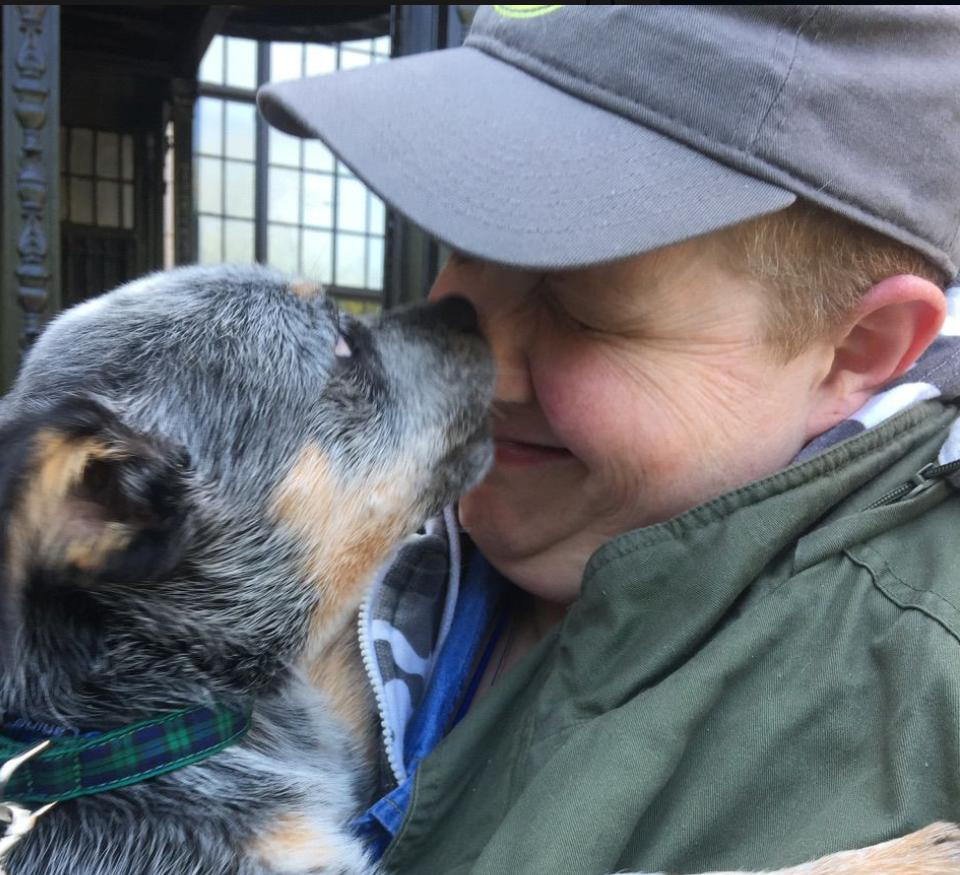 This is an image of Cal Montgomery. He is wearing a grey ballcap and olive jacket. A small cattle dog is licking his face playfully.