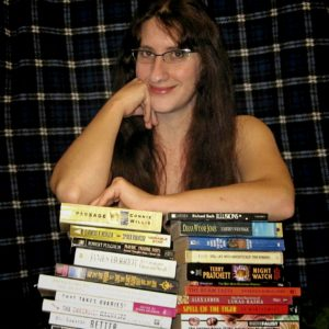 This is a picture of Ayana Bailin. She is a white woman leaning on a stack of books. She has long brown hair and wire-frame glasses.