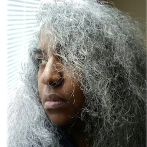 This is an image of Kerima Cevik. She is a black woman with long, curly gray hair. She is looking out a window into sunlight.