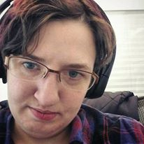 The image is of Kit, a white non-binary person with short brown hair tinged with reddish-purple, wearing glasses and over the ear headphones.