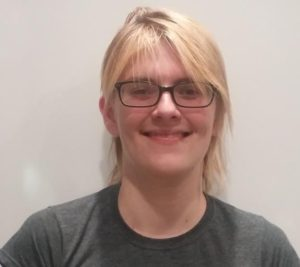 This is an image of Ozy Brennan. They are a nonbinary white person with medium length blond hair and black-rimmed glasses.