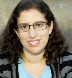 This is an image of Sarah Pripas Kapit. She has long dark curly hair and is wearing black wire frame glasses.