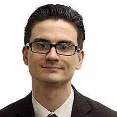 This is an image of Zack Budryk. He is a white man with dark hair and black framed glasses. He is wearing a suit and tie.