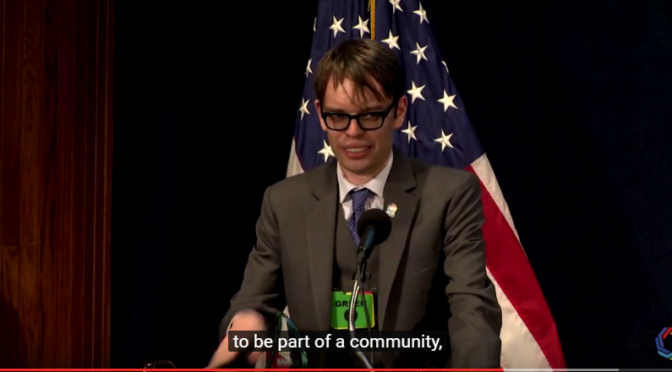 This is an image of Dylan Matthews at the ASAN Gala. He is a white man with brown hair and black, thick rimmed glasses. He is wearing a gray suit. In the foreground, there is an American flag.