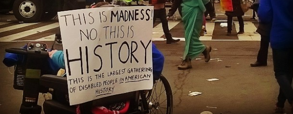 "This is an image of a wheelchair at the women's march, from behind. There is a poster stuck to the back of the wheelchair that reads: ""This is Madness! No this is history! The largest gathering of disabled people in American history!"""