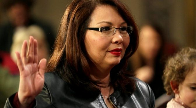 Tammy Duckworth is being sworn into office. She has long brown hair, glasses, and red lipstick. She is holding one hand on a Bible and the other in the air as she takes her oath.