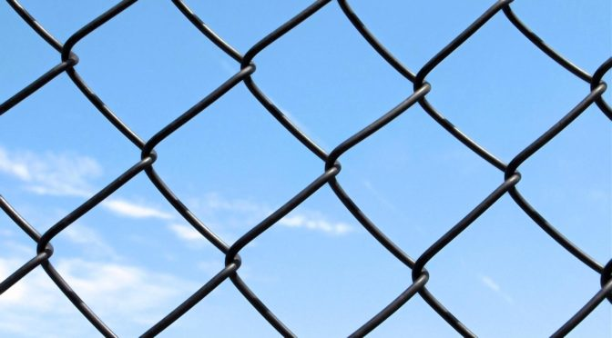 This is an image of a chain link fence. There is a blue, almost totally clear sky in the background.