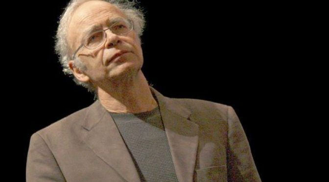 This is an image of Peter Singer. He is a white man with white hair and a receding hairline. Singer is wearing wire-frame glasses and a tan suit.
