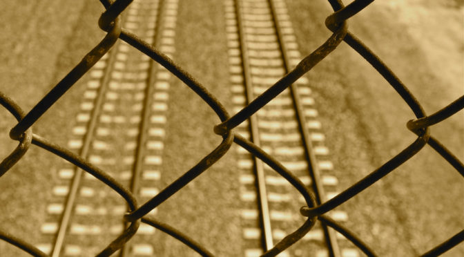 This is an image of a chain link fence. There are train tracks visible behind it.