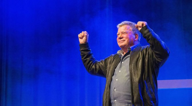 This is an image of William Shatner standing in front of a blue backdrop. His arms are raised.