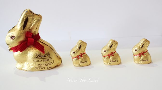 This is an image of a large chocolate Lindt gold bunny with three smaller gold wrapped chocolate