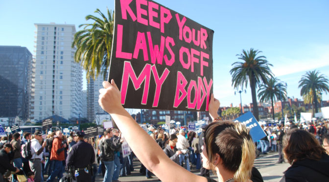 "This is an image of a woman in a crowd of protesters. She is holding up a pink sign that reads, ""keep your laws off my body."""