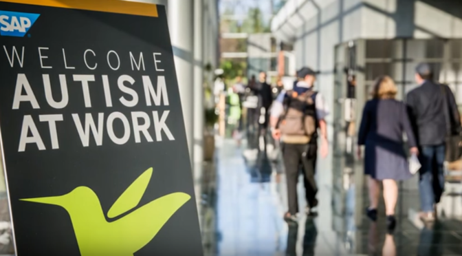This is a photo of the Autism at Work Conference sign, with people milling in the background.