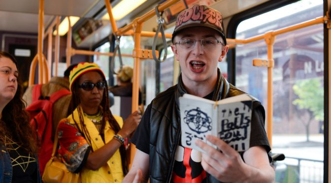 This is an image of Micah Fowler. He is standing on the bus reading from a chapbook.There are different people of diverse dress and backgrounds standing behind him.