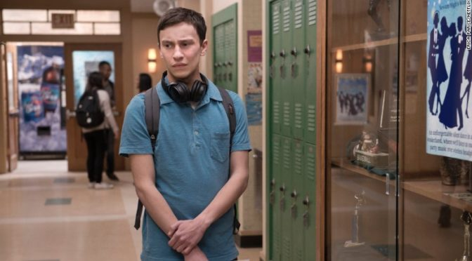This is an image of the main character in Atypical, Sam. he is walking down a high school hallway. He is wearing a blue polo shirt and has large black headphones around his neck.