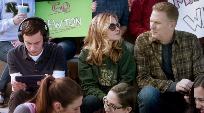 "This is an image of Sam and his parents sitting in the bleachers at a sports event. Someone behind them is holding a sign that says ""Go Newton!"""