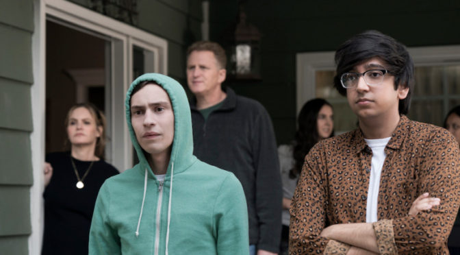 This is an image of Sam, Zahid, Doug, Elsa, and an unnamed teenage girl standing on a porch. Sam is wearing his favorite hoodie.