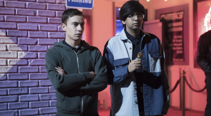This is an image of Sam, a white teen boy wearing a hoodie, and Zahid, a South Asian teen boy wearing a jacket, standing outside a strip club.