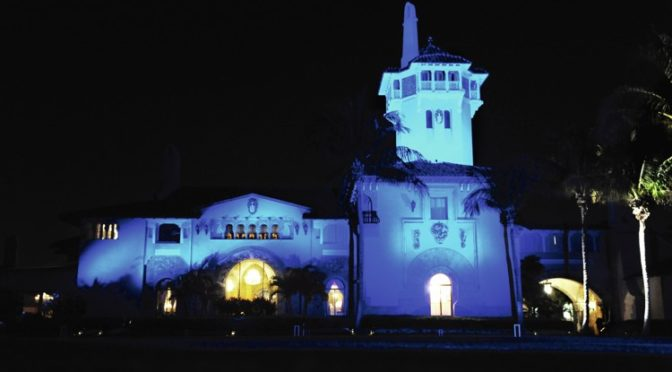This is an image of Mar-a-Lago's main building. It is bathed in blue light.