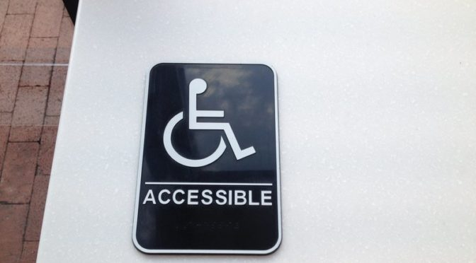 "This is an image of a wheelchair symbol with the text ""accessible"" underneath it. The symbol and text are white on a black background."
