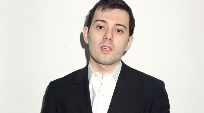 This is an image of Martin Shkreli. He is a white man with dark hair and dark eyes. He has a really annoying facial expression that kind of makes you want to punch him, even if you've never actually considered violence against anyone before. Also, he is wearing a black suit jacket with a white button down shirt.