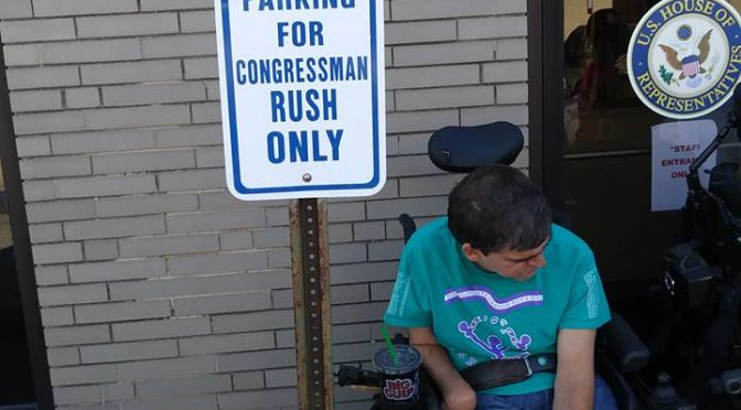 "A white man in a power wheel chair an and ADAPT t-shirt sits next to a sign that says, ""Parking for Congressman Rush Only."""