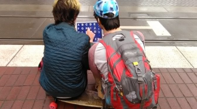 This is an image of two teenage boys sitting on a skateboard. One of the boys is holding a letter board used for alternative and augmentative communication purposes.