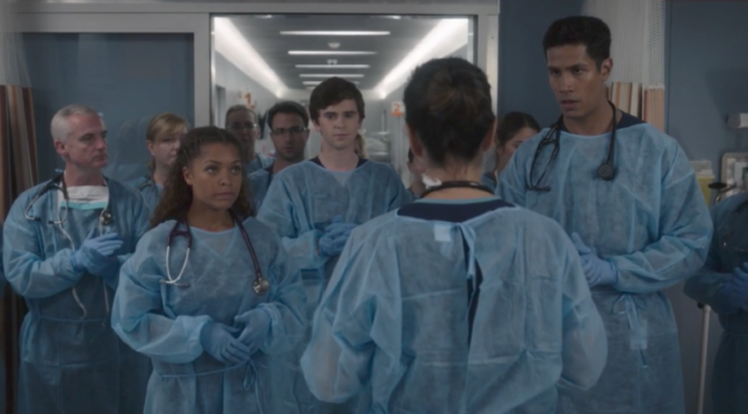 This is an image of a dozen doctors wearing surgical clothing. They are standing in a hospital hallway and waiting.