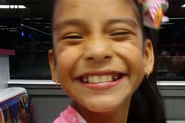This is an image of Rosamaria Hernandez. She is a young girl with brown skin and dark hair pulled back into a pony tail. She is wearing a pink shirt and smiling radiantly.