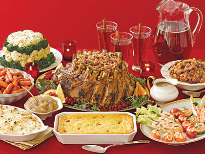 This is a colorful array of christmas dinner foods on a red background. There are multiple cassaroles and some kind of roast. Everything is sepia-toned -- The photo looks as though it might be from the 1970's.