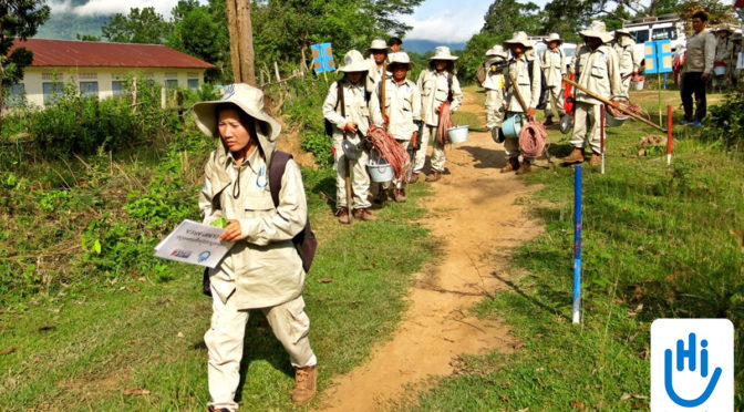 A group of Laotians wearing khaki uniforms walks through a grassy area. The man leading the group is holding a map. They are going to remove mines.