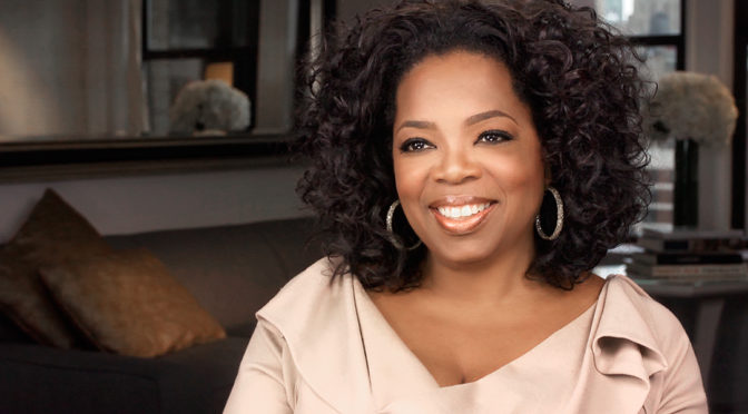 This is an image of Oprah Winfrey. She is a black woman with natural, loosely curled hair. She is wearing a peach colored, ruffled shirt and smiling. There is a living room in the background.
