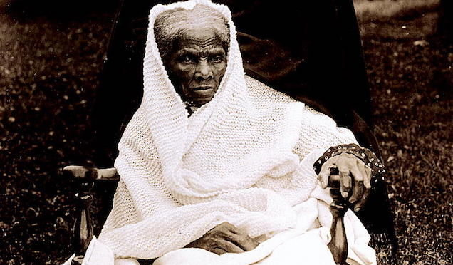This is an black and white photograph of Harriet Tubman from 1911. She is a thin, older black woman with a white shawl wrapped around her head. Tubman has a serious expression on her face. She is sitting in a wooden chair, and looks very much like a queen sitting in a throne.