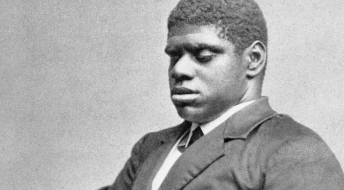 "This is an image of Thomas ""Blind Tom"" Wiggins. The photograph is in black and white and from the 1800's. Tom is a heavyset young black man wearing a shit jacket and bow tie. He is clean shaven and has close-cropped, curly hair. His eyes are closed."