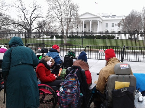 "This is an image of an assortment of protesters outside the white house. They area wearing heavy winter coats. Most of them are wheelchair users. One person has a ""Rev Up!"" sticker from AAPD's election campaign."