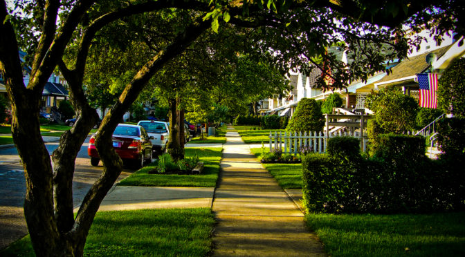 This is an image of a normal suburban American street. There are trees, green lawns, and a few ordinary sedans parked along the side of the road. The houses are small and well maintained.