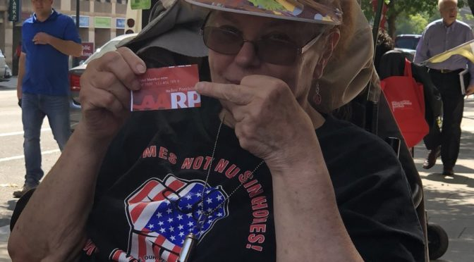 Daniese McMullin-Powell of Deleware ADAPT sticks her middle finger up at her AARP member card. She is an older white woman with red hair sitting in a power wheelchair.